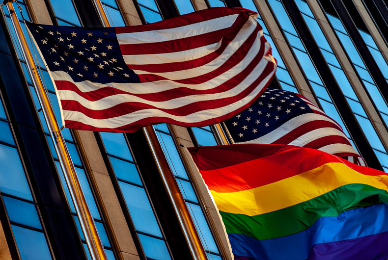Two American flags waving just above a Pride flag