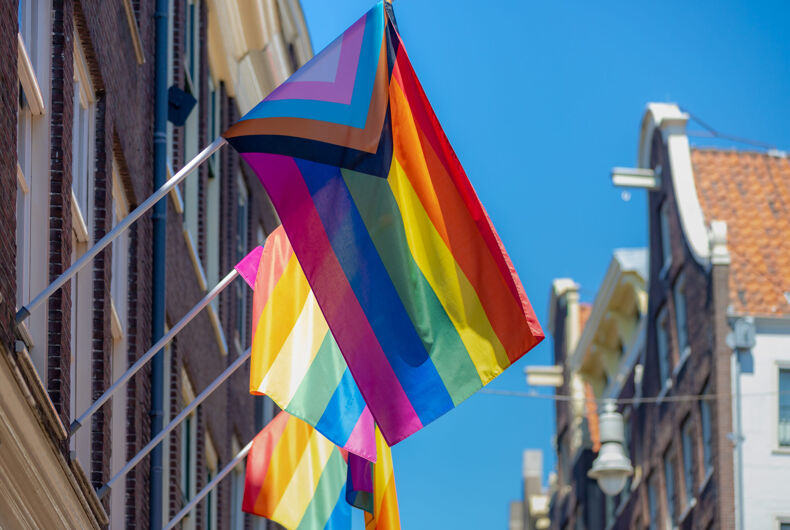 Progress pride flag (new design of rainbow flag) waving in the air with blue sky, LGBTQ community in Netherlands