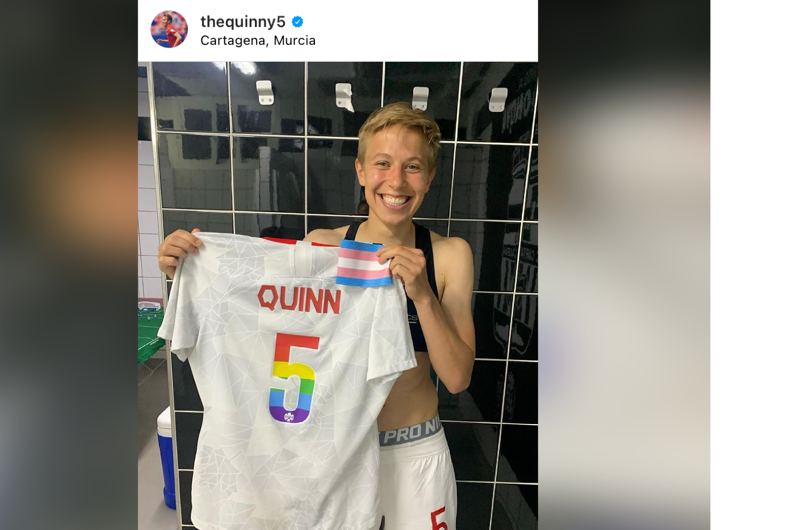 Soccer player Quinn holding up their Pride-colored jersey as well as a small trans flag.