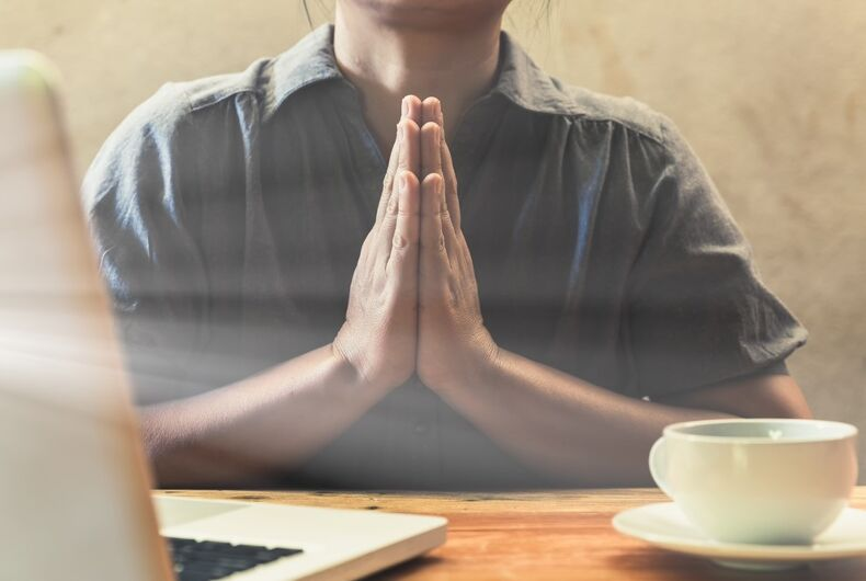 A computer worker praying. Also coffee. It's a stock image, not Lorie Smith.