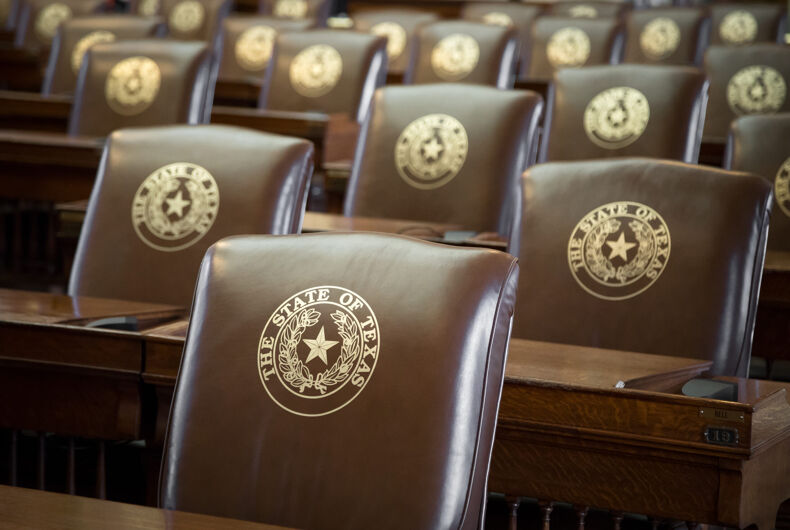 Rows of leather seats, with gold embossed The State of Texas and Lone Star seal, in the House of Representatives chambers at the capitol building