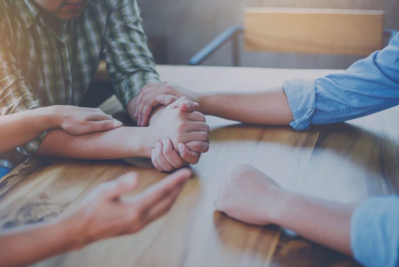 Christian people are praying for young man friends on wood table at church prayer room to encourage and support him in his problem and spiritual growth, small prayer group and fellowship concept