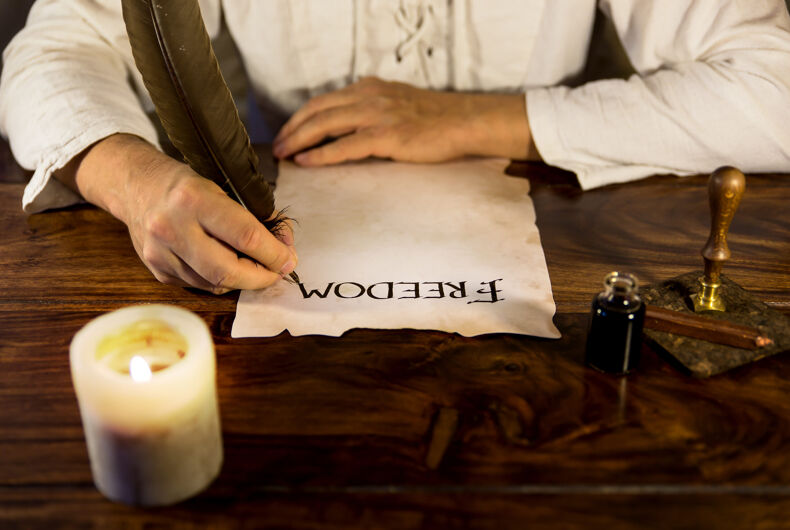 Man writing on parchment paper: freedom
