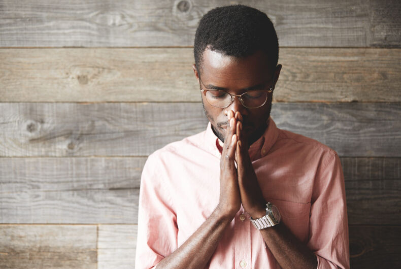 Young meditating and praying African American man wearing pink shirt and glasses, holding hands in prayer against his lips