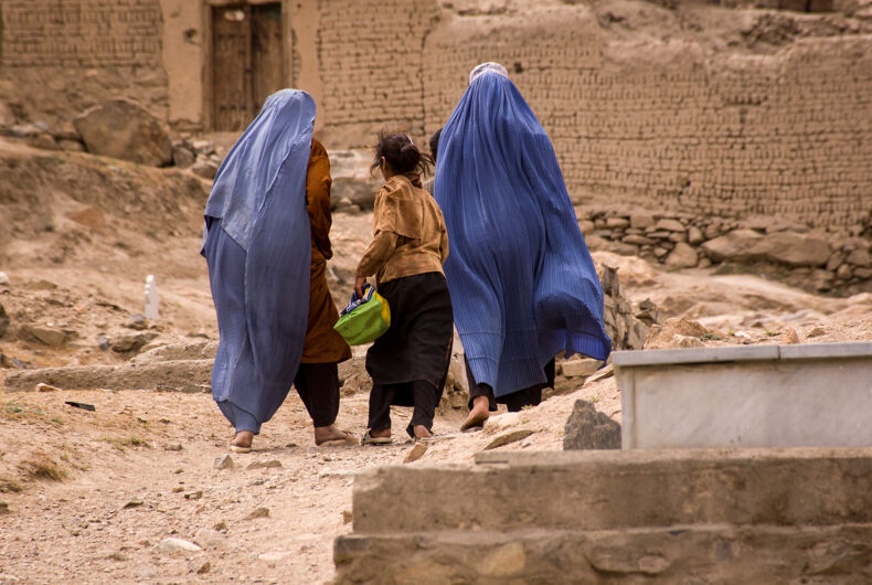 Two women and a girl walk through a graveyard in Kabul, Afghanistan