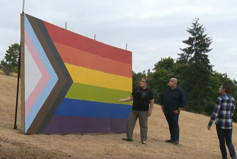 Erin and Jaybill McCarthy in front of their giant Pride flag