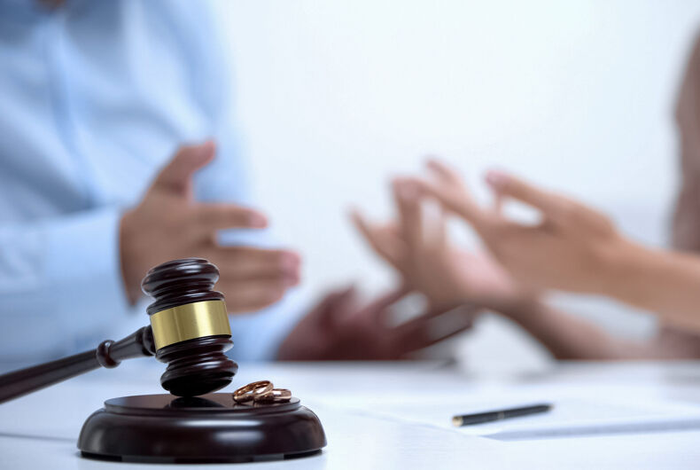 Spouses arguing about property division during divorce, gavel and rings closeup