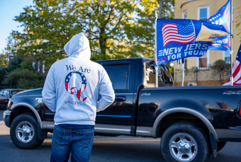 Weehawken, New Jersey, USA - November 2nd, 2020 - Day Before Election Day Trump Rally - Hooded man wearing a Qanon sweatshirt at Trump Rally with Truck and Flags in front of him .