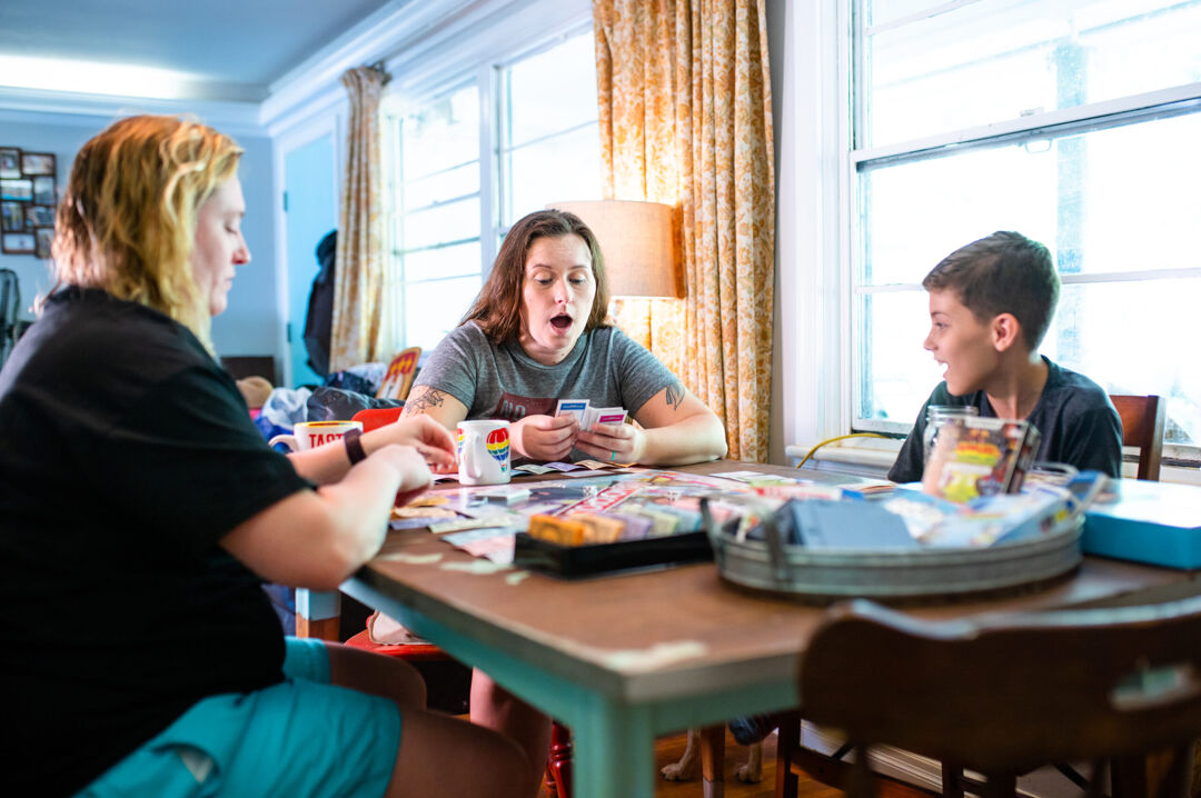 Two moms and son playing board game