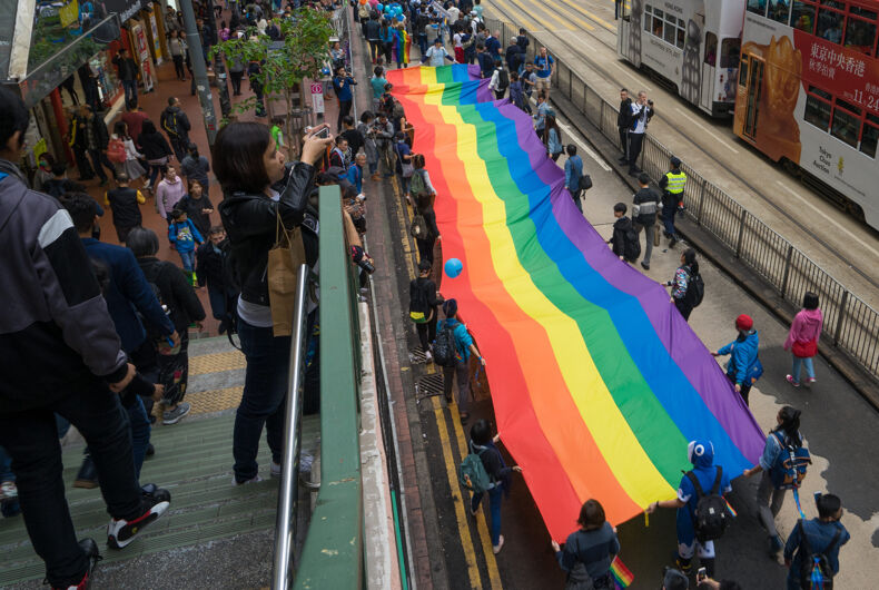 NOV 25, 2017: Passerby is taking photo of the long rainbow flag of the pride parade in Hong Kong.