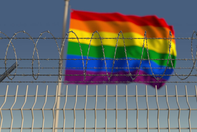 A rainbow flag behind barbed wire