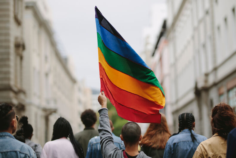 People marching, someone has a rainbow flag held up