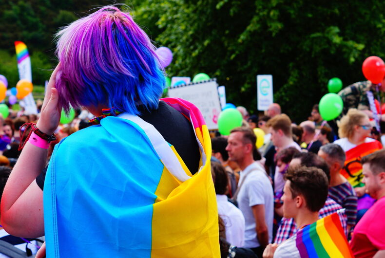 Edinburgh, Scotland - June 17 2017: Young person with coloured hair and pansexual pride flag around shoulders at Edinburgh Pride March